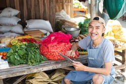 close up of the man selling the vegetable stall smiling while using the tablet pc in the vegetable stall background
