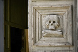 Close up of the medieval wooden door with skull and crossbones carved into it at the entrance to the Church of the Purgatory in Matera, Italy.