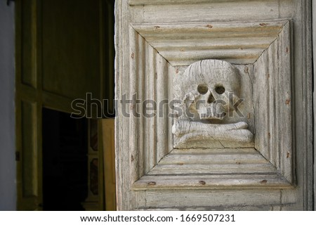 Photo of  Close up of the medieval wooden door with skull and crossbones carved into it at the entrance to the Church of the Purgatory in Matera, Italy.