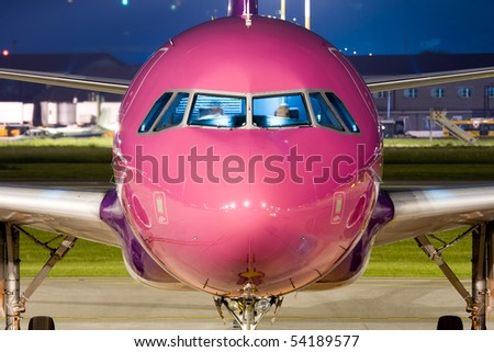 Close up of the nose of a violet airbus parked at night.
