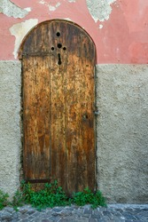Close-up of the old wooden door of an abandoned house with pink and gray weathered wall, Italy