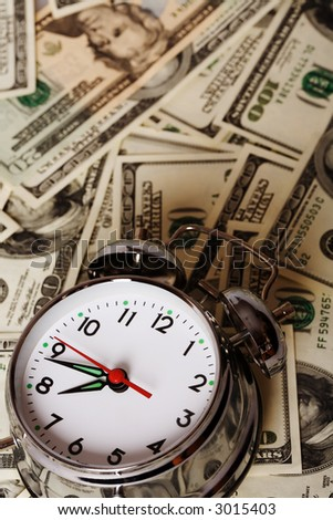 close up of the oldfashioned alarm clock with money