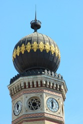 Close-up of the onion dome on an octagonal tower with clocks at the top of the Dohány Street Synagogue with a blue sky. Great Synagogue Tabakgasse, the largest in Europe, a centre of Neolog Judaism.