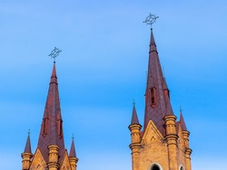 Close-up of the pinnacles of Church of the Transfiguration of the Lord against blue sky in Krasnoyarsk, Russia Catholic church was built in neo-Gothic style in 1908-1911.