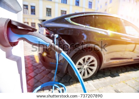 Close up of the power supply plugged into an electric car being charged #737207890