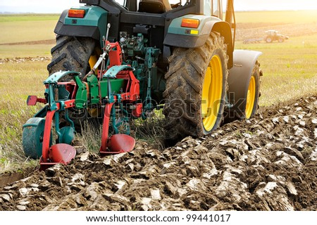 Close up of the rear end of a tractor while plowing