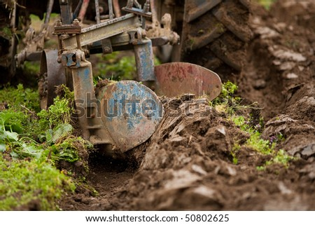 Close up of the rear end of a tractor while plowing, some motion blur present - stock photo