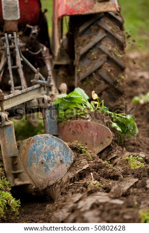Close up of the rear end of a tractor while plowing, some motion blur present