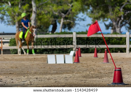 Close Up of the Red Flag of Start on Blur Man Riding a Horse in a Riding School during a Competition on Blur Background. Italy #1143428459