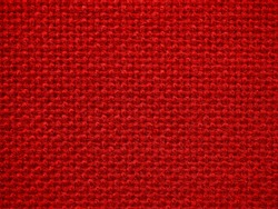 Close-up of the red textile texture, background and wallpaper. The texture of red fabric textile upholstery of furniture. High-quality macro photography.