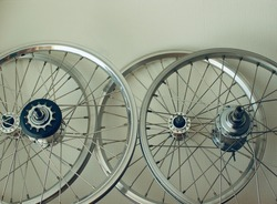 Close up of the rims and spokes of bicycle wheels.