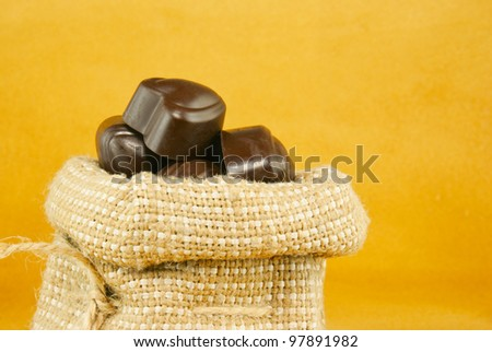 Close up of the sack full of chocolate candies over yellow background
