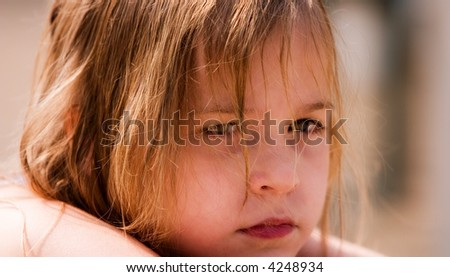 Close up of the serious face of a young girl, her hair wet after swimming.