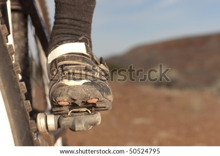 Close up of the shoe of a person riding a mountain bike in a desert landscape. Horizontal shot.