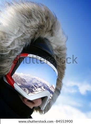 Close up of the ski goggles of a man with the reflection of snowed mountains - stock photo