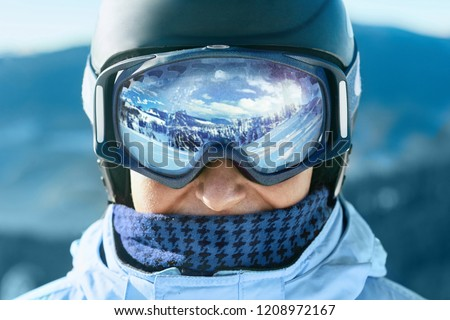 Close up of the ski goggles of a man with the reflection of snowed mountains.  A mountain range reflected in the ski mask.  Portrait of man at the ski resort on the background of mountains and sky #1208972167