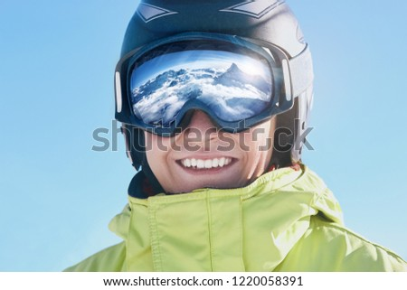 Close up of the ski goggles of a man with the reflection of snowed mountains.  A mountain range reflected in the ski mask.  Portrait of man at the ski resort.  Wearing ski glasses. Winter Sports.  #1220058391