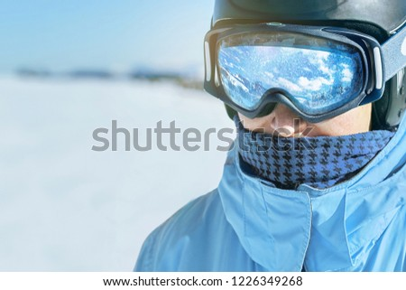 Close up of the ski goggles of a man with the reflection of snowed mountains.  A mountain range reflected in the ski mask.  Man  on the background blue sky. Wearing ski glasses. Winter Sports.  #1226349268