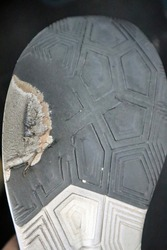 Close-up of the sole of a tattered running shoe