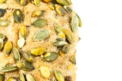 close up of the surface of a german bread roll with pumpkin seed topping