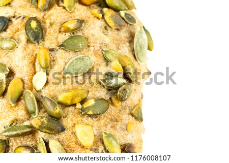 close up of the surface of a german bread roll with pumpkin seed topping #1176008107
