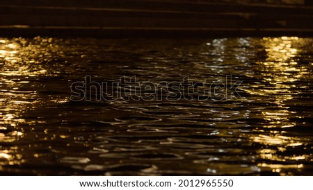 Close up of the surface of the water with the lights of the night city. Stock footage. Rippled wide rive and the dark city street on a summer night with walking people. Photo stock ©