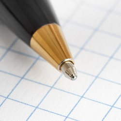 Close up of the tip of a ballpoint pen on the background of a sheet of checkered paper