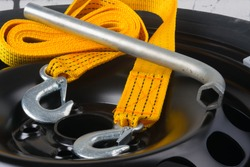 close-up of the tow rope and key for removing the wheel, against the background of the metal black disc of the car