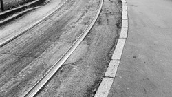 Close-up of the tracks of the tramway in a street of Milan, Italy. Tramway is a common public transportation mean in the city. Monochrome.