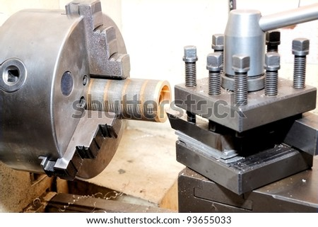 Close-up of the turning of a golden bezel on an old-fashion manual lathe - stock photo