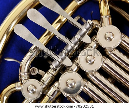 Close up of the valves and keys of a concert french horn on a dark blue background