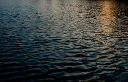 Close-up of the water surface of the lake. Sun reflecting on the water. Beautiful sunset. Nokhur Gol Lake, Qabala, Azerbaijan