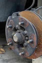 Close-up of the wheel hub without the wheel. Front wheel hub with studs and rusted brake disc. Auto shop. No people.