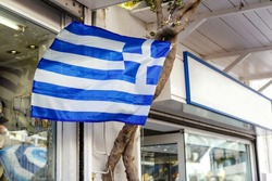 close-up of the white and blue national flag of Greece hanging on the street .The country's flag is flying in the wind.European Union