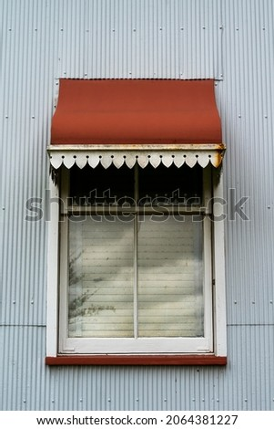 Close up of the window and red iron awning of a heritage listed historical homestead