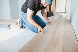 Close-up of the work of a master floating flooring installation - installing laminate on the floor - male hands during work