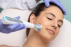 Close up of therapist doing facial mesotherapy treatment with flat head plasma pen. Electric impulse on woman's cheek stimulating new collagen.