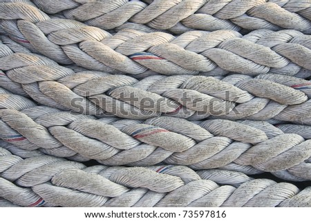 Close-up of thick textile ropes rolled on a spool