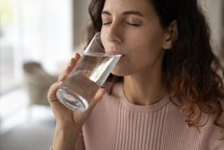 Close up of thirsty young Hispanic woman hold glass drink clean cold still mineral water. Dehydrated millennial Latino female enjoy clear aqua for body refreshment. Habit, diet healthy life concept.