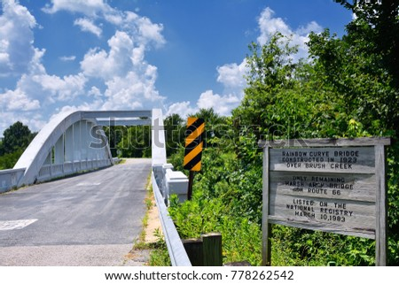 Close up of this Rainbow Curve Bridge Constructed in 1923 that is the only remaining Marsh Arch Bridge on Route 66. Route 66 signs are painted on the pavement. #778262542