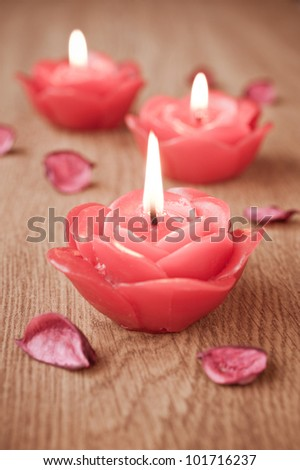 Close-up of three candles and flower petals
