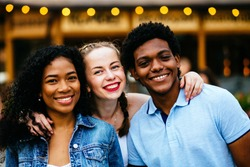 Close up of three multiethnic hipster teenagers friends laughing and hugging while spending time together outdoor over pub or cafe background.