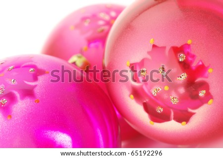 Close-up of three pink Christmas balls on white background.