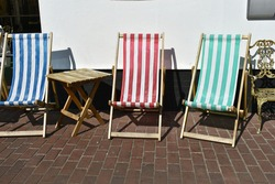 close up of three striped deckchairs with no one sitting in them, outside in the summer sunshine.  Pretty coloured seats,  red and white, blue and white. and green and white