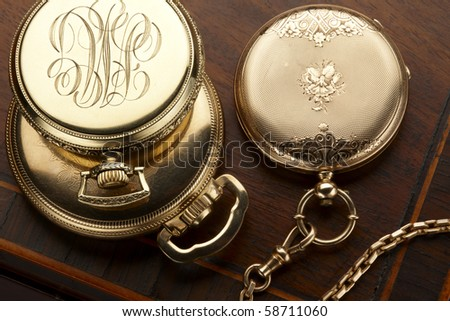 Close up of three vintage, gold pocket watches shot on antique wooden box