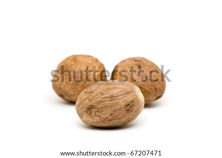 Close up of three whole nutmegs on white background