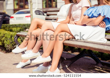Close up of three women with beautiful legs sitting on bench #524111554