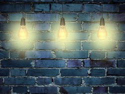 Close-up of three yellow turned on light bulbs on blue painted brick wall background