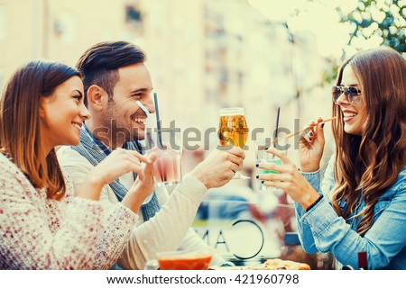 Close-up of three young cheerful people eating pizza and drinking beer outdoors.