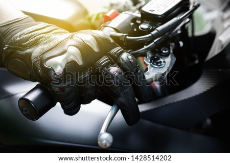 Close up of throttle control hand and brake lever motorcycle, Hands wearing black leather gloves with a protective card grip the brake lever